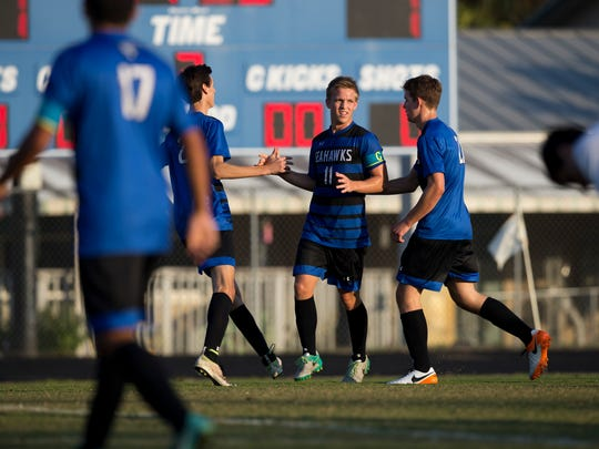 Community School of Naples' senior Aaron Harris (11) is congratulated by teammates after scoring a goal against Seacrest Country Day Friday, Jan. 20, 2017 in Naples.