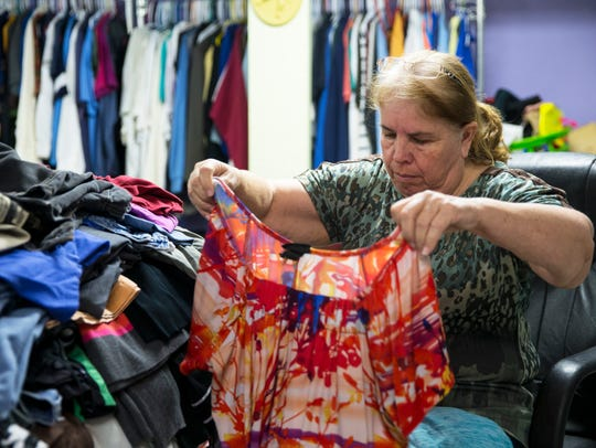 Maria Hernandez folds clothes for guests to have after