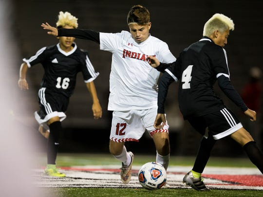 Immokalee's Carlos Trigueros (12) dribbles through Mariner's Robert Franco (16) and Esteban Orjuela (4) in the first half of action during the Class 3A regional quarterfinal Wednesday, Feb. 1, 2017 in Immokalee. Immokalee took a 2-0 lead into halftime.
