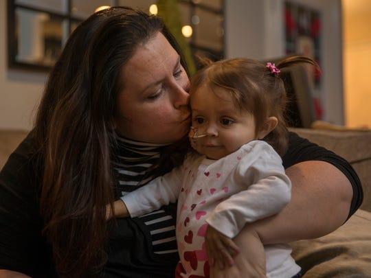 Farra Rosko kisses her 1-year-old daughter Talia, who