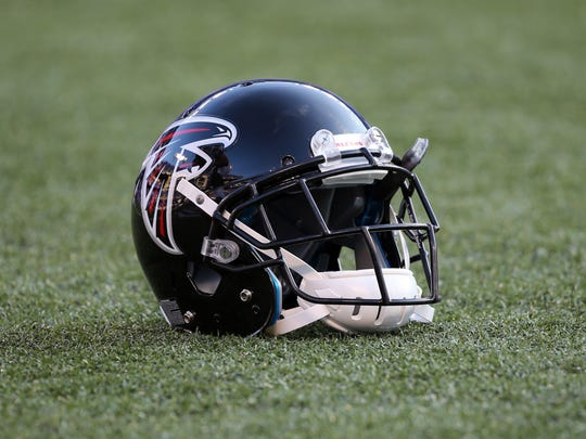 The helmet of an Atlanta Falcons player sits on the turf.