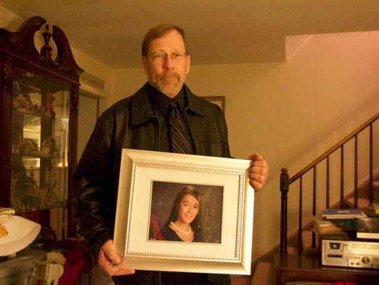 Michael Stern holds photo of his daughter Sarah.  Authorities