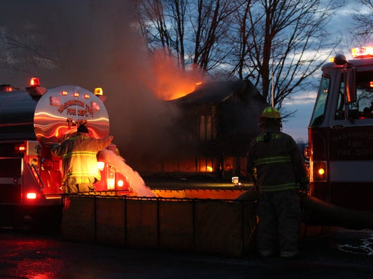 A Washington Township firefighter draws water from