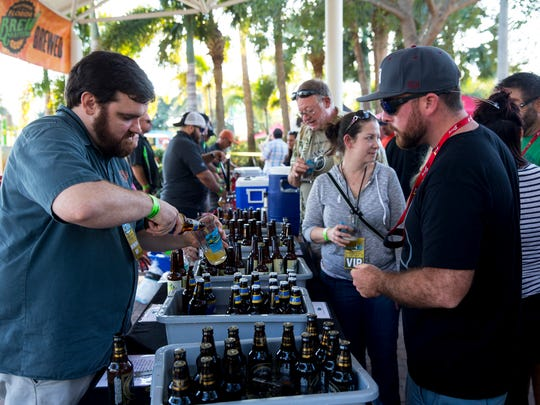 Ben Sisk, left, of Cavalier Distributing pours a sample of craft beer during Bonita Brew Fest at Riverside Park in Bonita Springs, Florida on Saturday, Feb. 4.