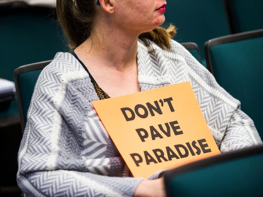 Michelle Herald of Cape Coral holds a sign in protest
