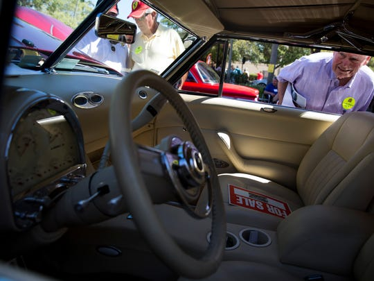 """Naples resident Jerry Werner checks out the interior of an old Cadillac along Fifth Avenue South during the 'Cars on Fifth' car show Saturday, Feb. 11, 2017 in downtown Naples. """"I'm not looking to buy anymore my wife will kill me,"""" Werner said with a smile."""