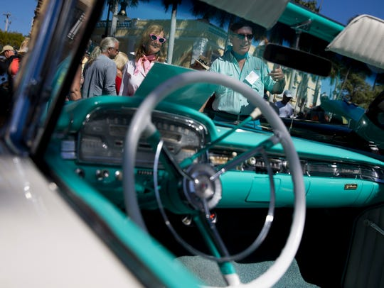 Natalie and Daniel Disco smile as they are greeted by onlookers along Fifth Avenue South during the 'Cars on Fifth' car show Saturday, Feb. 11, 2017 in downtown Naples. T