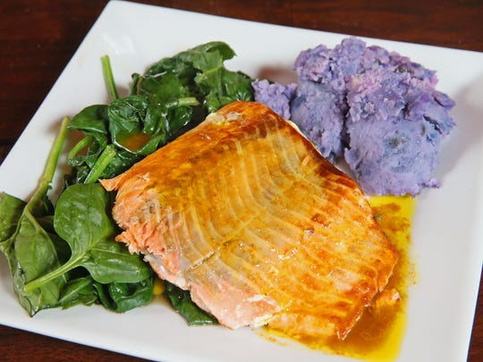 Seared salmon is topped with carrot-curry reduction and served with spinach and purple potatoes.
