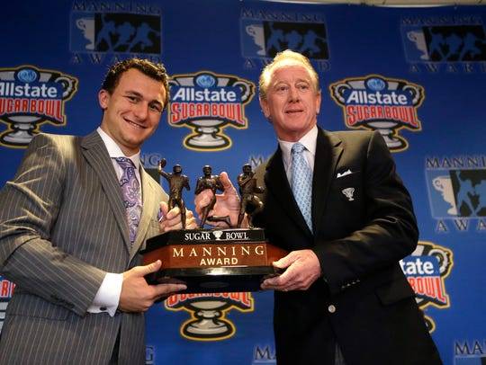Texas A&M quarterback Johnny Manziel, left, poses with  Archie Manning and the the Manning Award, which Manziel received as the nation's top quarterback on May 2, 2013. Six years later, Manziel is trying to get his career back on track in Memphis.