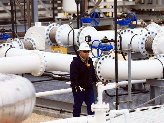 A docksman walks around pipes as crude is placed in