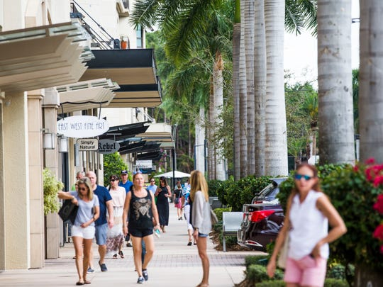 People walk around the shops at Mercato in Naples on Tuesday, Feb. 21, 2017.