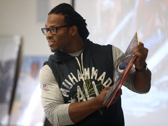 Quentin Gause, a former Bishop Kearney football star  is now a linebacker with the Denver Broncos, reads to a group at David Gantt Recreation Center.