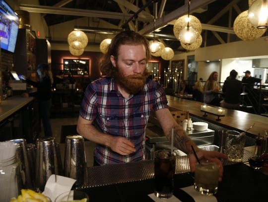 Ethan McCune makes a drink inside Okra on Jan. 27,