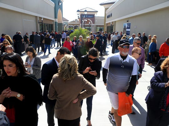 Shoppers walk around after the ribbon cutting for the