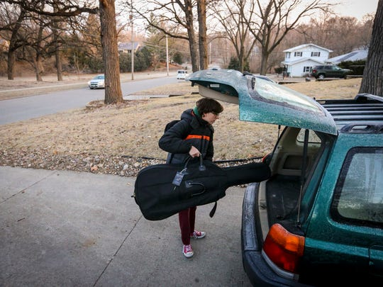 Rachel Brauch loads her cello into the family car at 7:15 a.m. Friday to head to orchestra practice at Meredith Middle School. Des Moines Public Schools is considering later start times for middle and high school students.