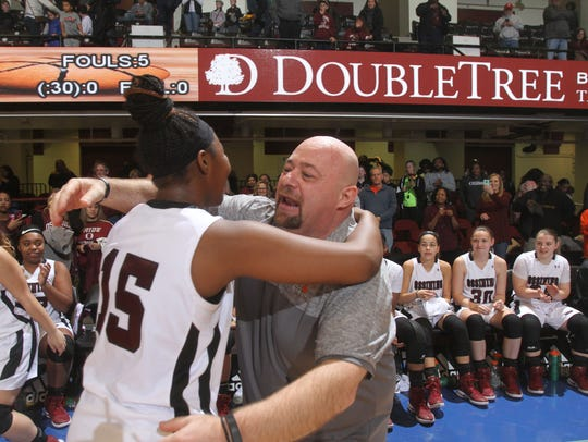 Ossining coach Dan Ricci (right) embraces a player following a championship game at the County Center.
