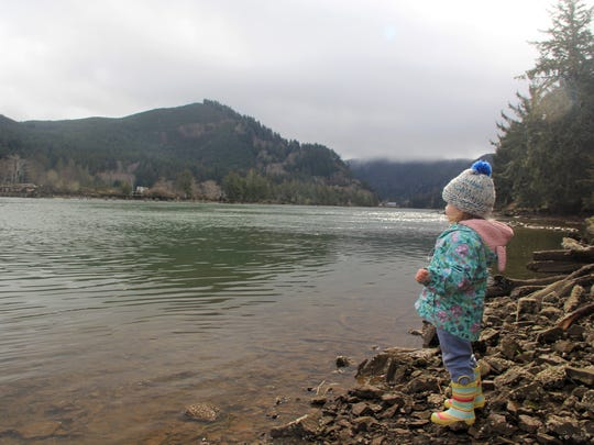 Lucy Urness, 2, looks out on the Siletz River after