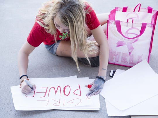 Sally D'Arcangelo, 13, makes signs while she joined other women who came to Arizona State Capitol to act together for equity, justice and the human rights of women and all gender-oppressed people, through a 1 day demonstration of economic solidarity during  International Women's Day on March 8, 2017.