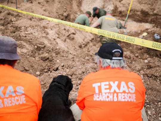 Orion, a human remains detection dog, sits between Texas Search and Rescue workers as a Tom Green County Sheriff's Office crew uncovers a the body of Naomi Michelle Miller on March 8, 2017, at the former San Angelo Speedway on Farm-to-Market Road 2105.