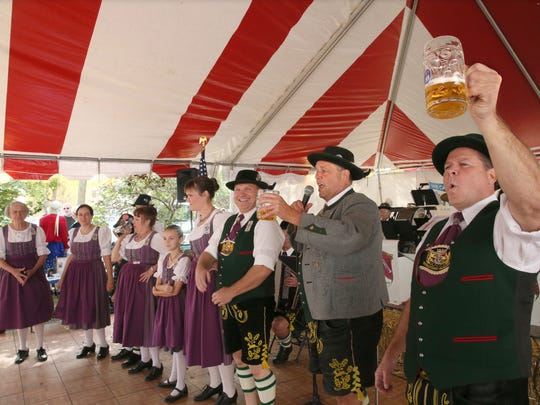 Robert Forster of West Allis (second from right) and Craig Leiner of Wauwatosa at right, lead fellow members of Wendlstoana Milwaukee, a German dance club founded in Milwaukee in 1927, in singing a traditional German toast as they hold steins of beer aloft at an Oktoberfest celebration.