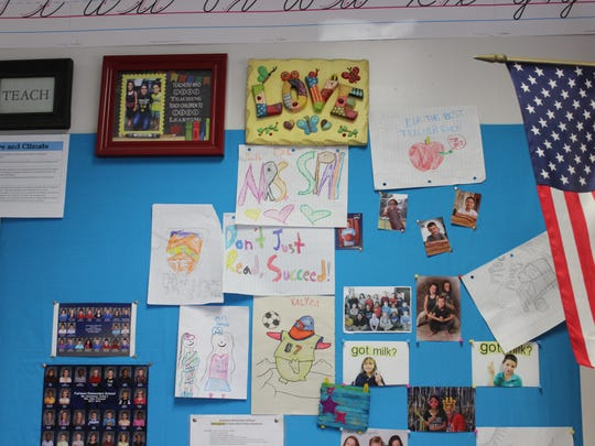 Notes and photos from students adorn Andrea Spall's classroom wall.