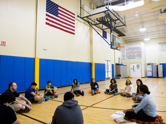 Teens sit in a circle during a group session on the
