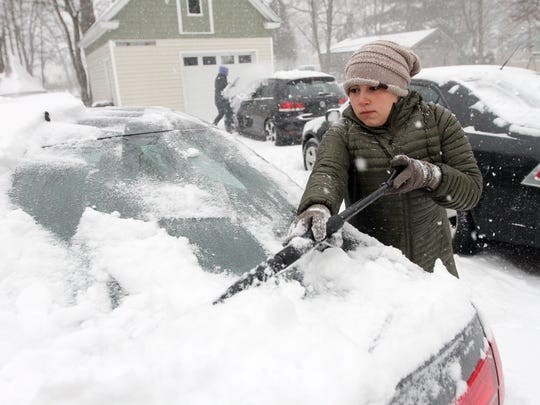 Chris Kazanjian, l, and Dana Windt of Morristown clean off their cars as a Nor'easter blasts N.J. and the Northeast with heavy snow, high winds. The late-winter storm is expected to drop as much as two feet of snow on Morris County. March 14, 2017, Morristown, NJ