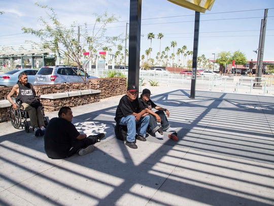 Homeless man sits in the shade at 19th Ave near Dunlap light rail station in March 2017.