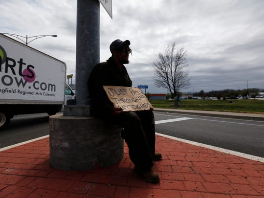 Jeff Walters holds up a sign while panhandling near