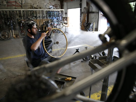 Volunteer Justin Rice works on adjusting a bike wheel's