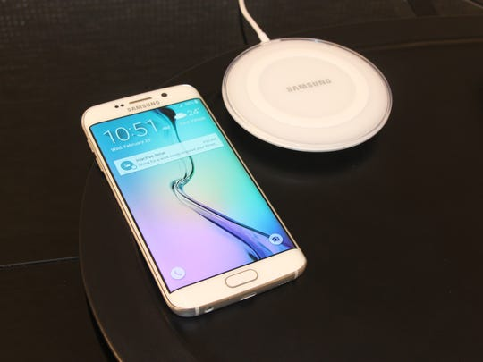 A Samsung Galaxy S6 Edge next to wireless charging