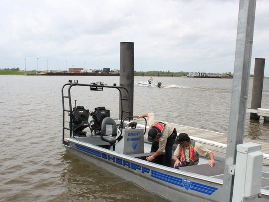 Grant Parish Sheriff's deputies ready one of the department's boats to go out on the Red River while another one passes behind it.