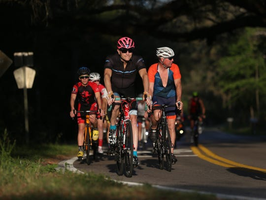 Nearly 100 cyclists gather at a sunny roadside spot on Baum and Capitola Roads Wednesday after a memorial ride in honor of Stephen Reker, 60, who died Tuesday evening after being hit by a car while riding his bike near Wadesboro Road, just east of Interstate 10.