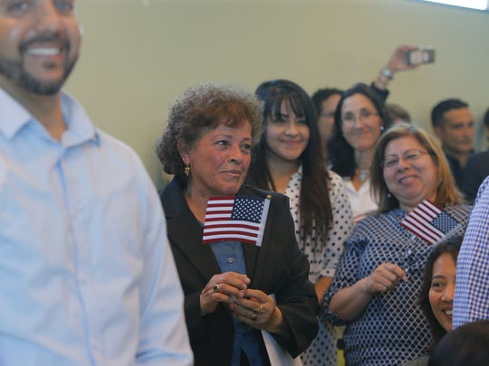 Antonia Rubalcava of MExico (center) smiles during her naturalization ceremony on Friday.