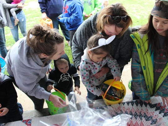 Kate Raben (left) and Jayna Doehring (right) help Finn (center left), 4, and Mae (center right), 2, Raben pick their prizes