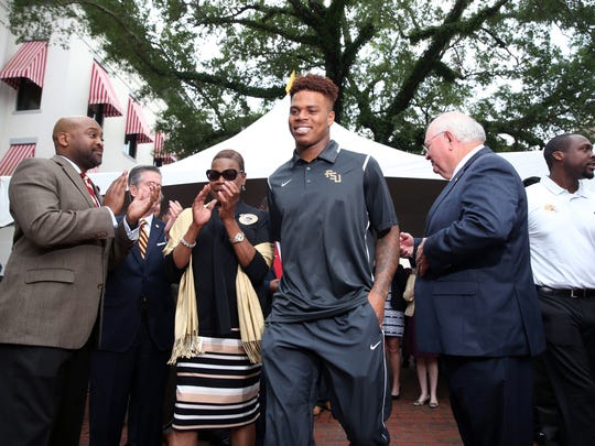 Quarterback Deondre Francois is applauded as he walks on to the Historic Capitol's steps during Florida State University's Day at the Capitol event on Tuesday, April 4, 2017.