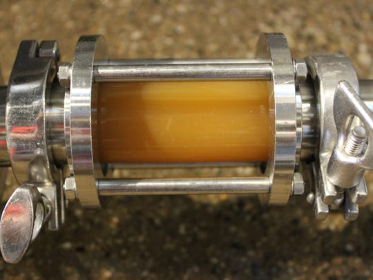 A sight glass showing the general color and consistency of an unfermented, experimental New England-style IPA, prior to going into the fermentation tank Sept. 24, 2016 at Old Nation Brewing Co. in Williamston.