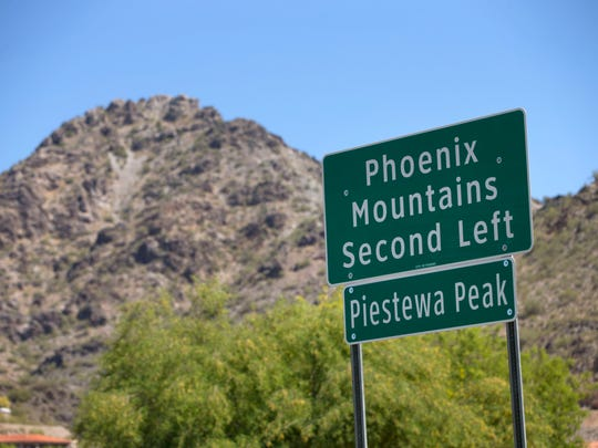 A sign on Lincoln Drive near the intersection of Squaw Peak Drive in Phoenix directing traffic to Piestewa Peak.
