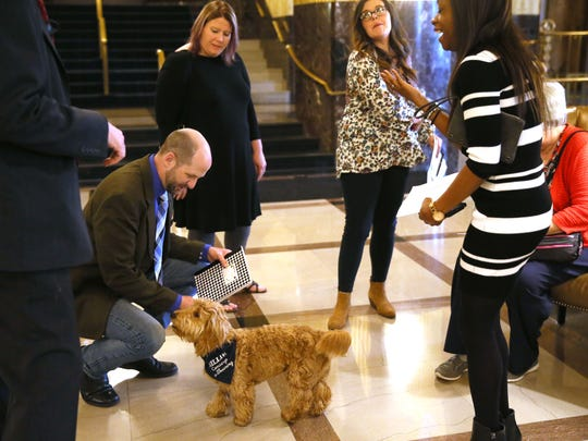 "Millie, the ""canine concierge"" at the Hilton Milwaukee City Center, introduces herself to Alan Melot (lower left) of Joplin, Mo., as other hotel guests look on."