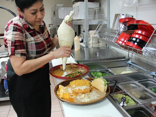Eva Lopez adds sour cream to two lunch plates at Casa Rojas Mexican Restaurant & Cantina.