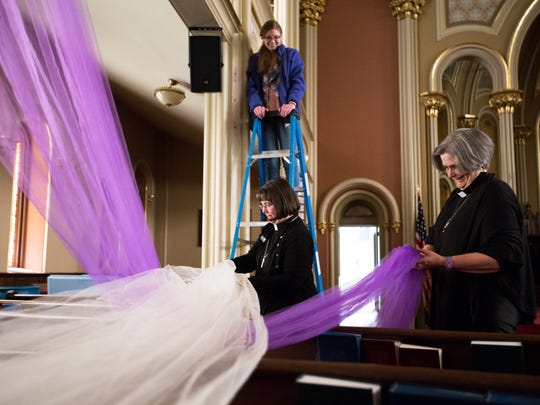 Emma Kindig, on ladder, Associate Pastor Becky Kindig, center, and Rev. Kimberly Chastain, hang purple and white tulle at United Presbyterian Church ahead of Easter Sunday on Thursday, April 13. In Christian faiths the color purple is often used to represent penitence and is associated with Lent, while white represents purity and is often associated with resurrection.