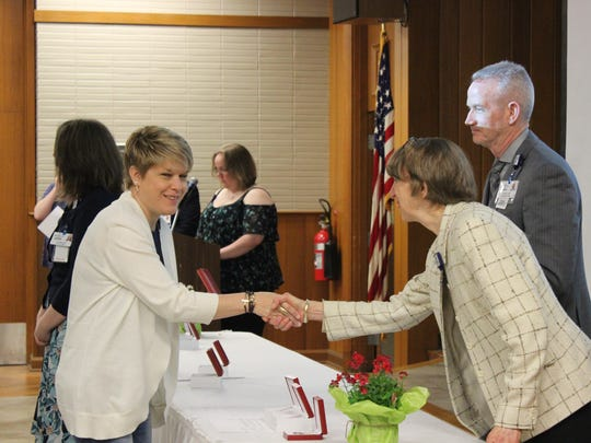 Deaconess President and CEO Linda White (right) shakes Tara Gray's hand (left) after she receives her award