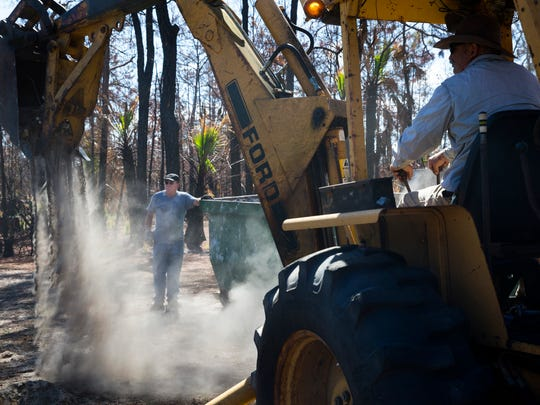 Laurence LeBuff, left, works with Robert Kirkland, Jr. to clear any remaining brush fire debris from his land in East Naples on Thursday, April 13, 2017. LeBuff plans to rebuild his home that burned down from the Lee Williams Fire in March.