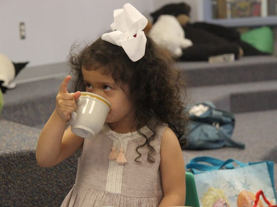 Kaydence Chavez, 3, practice table manners and etiquette during a tea party at Carlsbad Public Library.