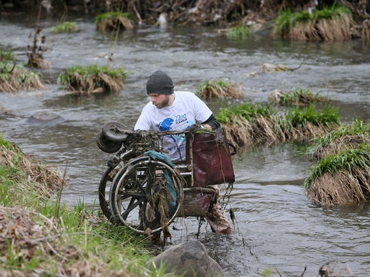A volunteer removes a wheelchair from Lincoln Creek during Milwaukee Riverkeeper's Spring Cleanup in 2017.