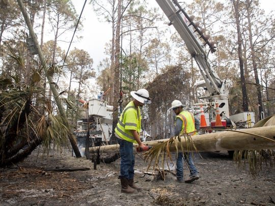 Employees of PowerTown Line Contruction,  contractors with Florida Power & Light, repair a row of downed power liens along Inez Road Saturday, April 22, 2017 in Golden Gate Estates.