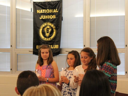 Newly inducted members of the John Paul II Jr. Beta Club, Abby Jones, Drew Ann Sprague, Sydnie Vessels, and Madison Morris participate in the candle lighting ceremony.