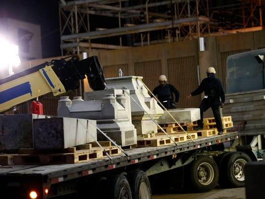 Workers dismantle the Liberty Place monument Monday,