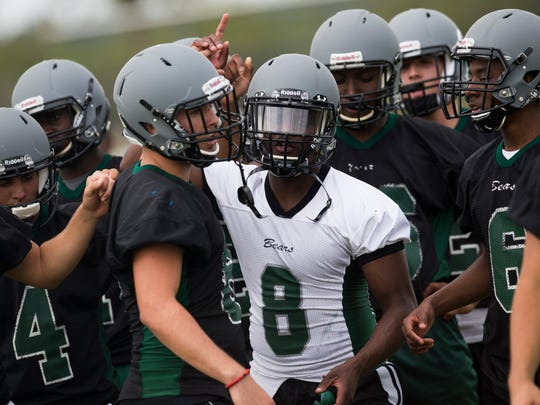 DeMarcus Townsend (8), a transfer from Gulf Coast High School, leads his new teammates in a huddle during Palmetto Ridge High School's first spring practice Monday, April 24, 2017 in Naples.