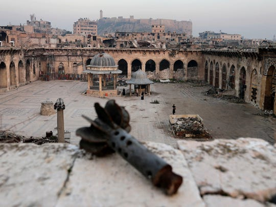 A mortar shell is seen in the foreground as people visit the heavily damaged Grand Umayyad mosque while the Citadel of Aleppo is seen in the background, in the old city of Aleppo, Syria, Thursday, Jan. 19, 2017. Government forces captured all parts of eastern Aleppo in December 2016, bringing Syria's largest city to full control of Syrian authorities for the first time since July 2012. The capture of Aleppo was President Bashar Assad's biggest victory since the country's crisis began nearly six years ago.